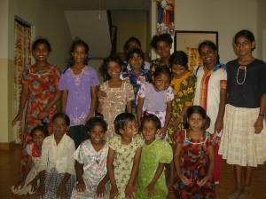 Some of the children in the school room with a teacher.